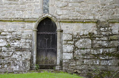 Wooden door in 14th century stone church wall. An old, wooden, oak door, blackened with aged and decorated with wrought iron features, set in the old stone wall Royalty Free Stock Photos