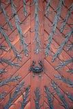 Wooden door. Heavy wooden door with smithery and metal handle Royalty Free Stock Image