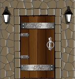 Wooden door. In the stone wall old wooden door, alongside two lantern Royalty Free Stock Photos