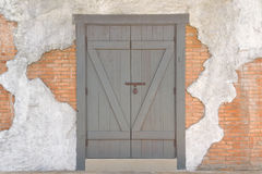 Wooden door. On the wall in bad disrepair Royalty Free Stock Photos