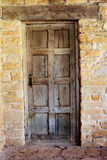 Wooden Door against Worn Stone Wall Stock Photos
