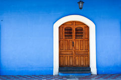 Wooden door and blue wall stock image
