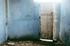 Wooden door on blue walls opening to light Royalty Free Stock Photos