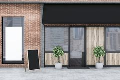 Brick restaurant exterior wooden doors, banner. Wooden door of a brick restaurant with potted plants standing outside. A blank poster in the window. Small Royalty Free Stock Images