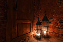 Wooden door in brick room with candles. Winter Is Coming Royalty Free Stock Photo