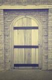 Wooden door on brick wall Stock Photography