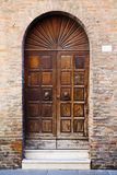 Wooden door in brick wall of medieval house Stock Images