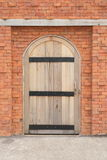 Wooden door in a brick wall Stock Images