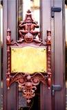 Wooden door with bronze plaque Stock Photography