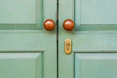 Wooden door with brown knobs. Green wooden door with brown knobs Stock Photography