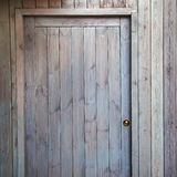 Wooden door on building with golden lock - background. Stock Photos