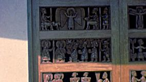 Wooden door church in Lagos Nigeria. Lagos, Nigeria, Africa - circa 1977: decorations on a wooden door of a small church in the city center. local black people stock video