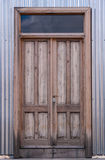 Wooden door in corrugated metal Stock Images