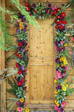 Wooden door decorated with flowers Royalty Free Stock Photo