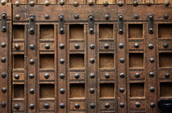 Wooden door detail. Close up of wooden door adorned with nails Royalty Free Stock Photo