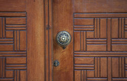 Wooden door detail. Close-up of the handle and keyhole of a decorative wooden door Stock Images