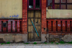 The wooden door of dilapidated building in a city Stock Photo