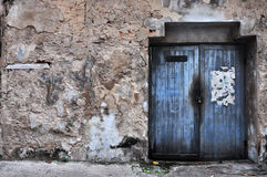 Wooden door in the dirty wall. At thailand Royalty Free Stock Images