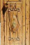 Wooden door with door knocker. Close-up view of a wooden door with old-fashioned door knocker made of brass Royalty Free Stock Image