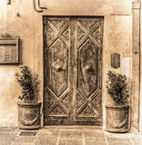 Wooden door and flower pots in sepia tone. Italy Royalty Free Stock Photography