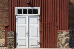Wooden door in front of stony house Stock Photos