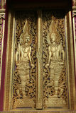 Wooden door with gold in the Thai temple Royalty Free Stock Image