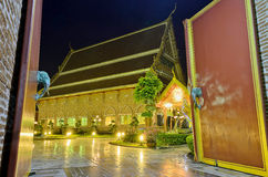 Wooden Door and Golden Buddhist Temple at Night Stock Photos