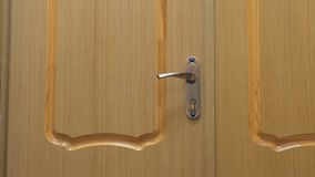 Wooden door with handle and lock, closeup view. Wooden door with metal handle and lock indoors, closeup view stock footage