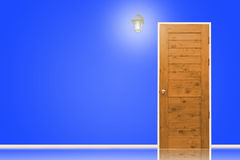 Wooden door and lamp with isolated blue wall texture. Royalty Free Stock Image