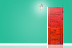 Wooden door and lamp with isolated green vintage wall texture. Stock Photos