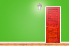 Wooden door and lamp with isolated green wall texture. Stock Photo