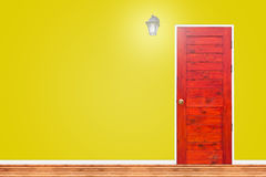 Wooden door and lamp with isolated yellow wall texture. Stock Photography