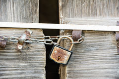 A wooden door locked with a chain and a rusty padlock. A wooden door locked with a chain stock photography