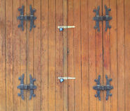 Wooden door locked by padlocks Stock Images