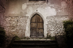 Wooden Door. Massive wood door on a stone wall Royalty Free Stock Photo