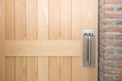 Wooden door with metal handle Stock Photography