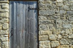 A wooden door with metal hinges is installed in the wall of an ancient stone. What does it conceal stock photo