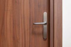 Wooden door with metal knob. Stock Image