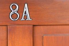 Wooden door with metal sign Stock Photo