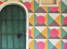 Wooden door and multicolor wall Royalty Free Stock Images