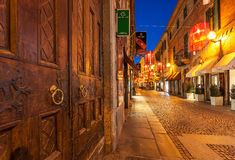 Wooden door and narrow street of Alba at night. Stock Image