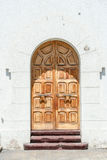 Wooden Door. An old brown wooden door on a white wall Royalty Free Stock Photography