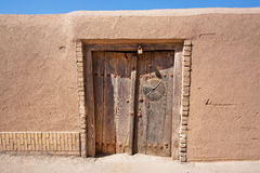 Wooden door of an old clay house in the Middle East Stock Image