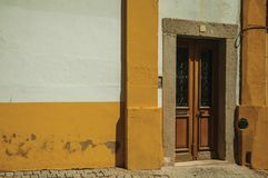 Wooden door in an old colorful building. Wooden door with stone door frame in an old colorful building on sunny day, in a deserted street of Elvas. A gracious royalty free stock images
