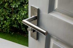 Wooden door opening with blur garden background. Knob, access stock image