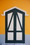 Wooden door on orange wall. Background Stock Photography