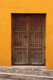 Wooden door in orange wall Stock Photography