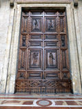 Wooden door with ornaments to the church in Assisi, Royalty Free Stock Image