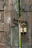 Door Chain. Vertical photo detail from an ancient wooden door with a chain and padlock on it Royalty Free Stock Photo