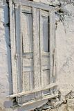 Wooden door painted white in stony wall covered with falling off plaster Royalty Free Stock Photo